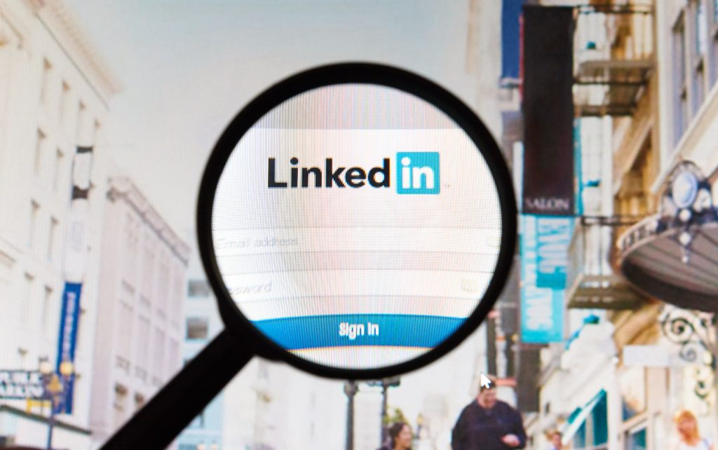 A magnifying glass hovers over the LinkedIn logo, with a cityscape in the background.