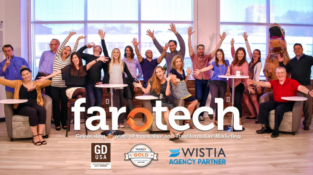 Farotech Digital Marketing Agency employees gather against a window, their hands in the air, covered by the Farotech logo.