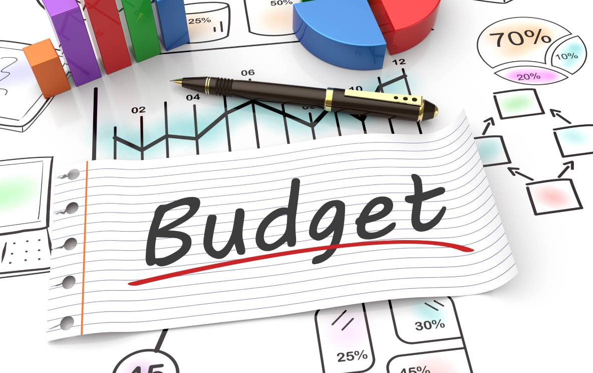 """The word """"budget"""" is written on a piece of paper, lying on a desk amidst calculations, graphs, and expense projections."""
