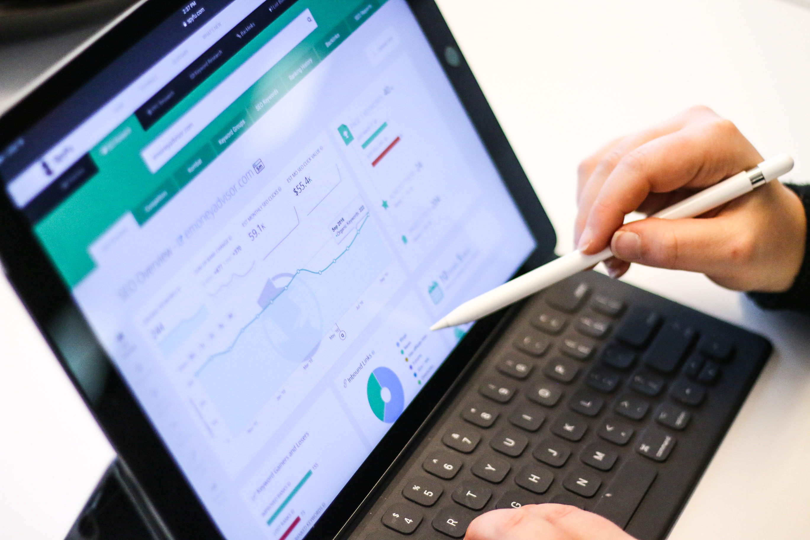 A stylus points to a tablet screen, showing the metrics for a business' marketing campaign.