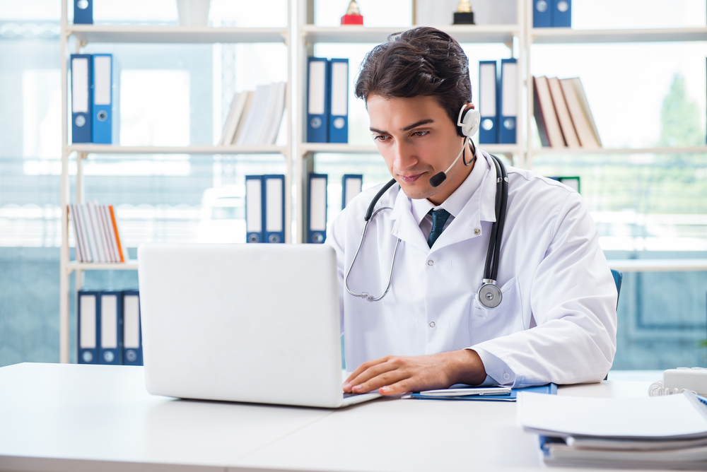 A physician sits at a desk in his office, consulting with a patient online during a telemedicine call.