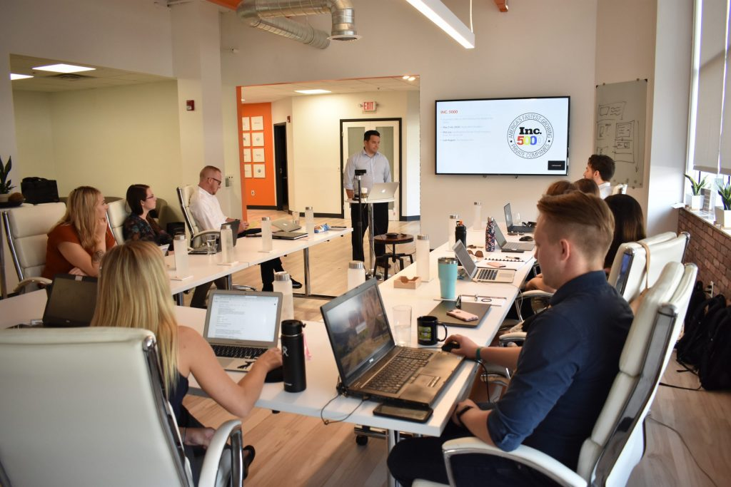 The Farotech marketing team gathers around a conference room to research and develop a Gap Assessment for a client.