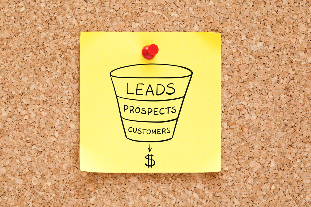 """A sticky note on a corkboard displays a sales funnel drawing labeled """"leads, prospects, and customers,"""" with a dollar sign."""